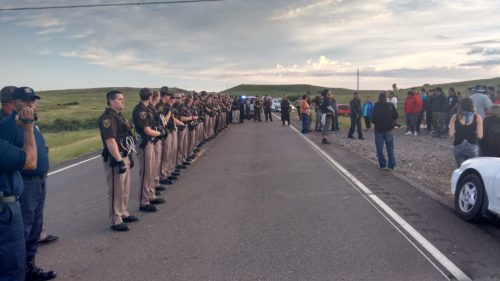 Law enforcement officers line up along a road in Morton County, North Dakota, Aug. 15 to block protestors who oppose the Dakota Access Pipeline that would run from the Bakken oil fields in the northwest part of that state to Illinois. Photo: Standing Rock Dakota Access Pipeline Opposition via Facebook