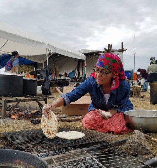 Osh Johnson, de la nación diné [o navaja] hace pan para el almuerzo en el campamento de las Piedras Sagradas, uno de los tres campamentos que se han plantado junto al río Cannonball en Dakota del Norte para albergar a los manifestantes que protestan contra el Oleoducto para el Acceso a las Dakotas. Foto de No Dakota Access in Treaty Territory – Campamento de las Piedras Sagradas.