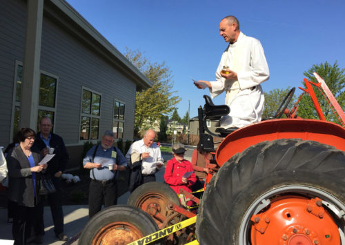 The Rev. Jim Eichner, rector of the Episcopal Church of the Holy Cross in Redmond, Washington, blesses a Food Bank Farm vehicle. Photo: Episcopal Church of the Holy Cross