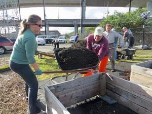 Unos voluntarios llenan de tierra un arriate elevado en el huerto de la Misión a los Marinos en Seattle. Foto de la Misión a los Marinos en Seattle vía Facebook.