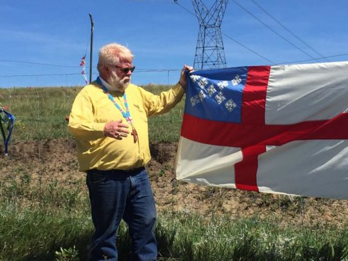 The Rev. John Floberg stands near an Episcopal Church flag that was added to the flags of other organizations and tribes participating in the protest against the Dakota Access Pipeline. Photo: John Floberg Facebook page