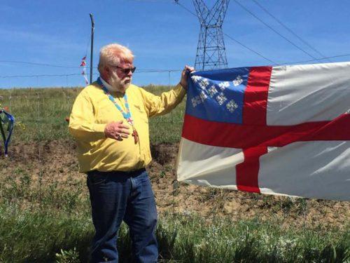 El Rdo. John Floberg posa junto a una bandera de la Iglesia Episcopal que se sumó a las banderas de otras organizaciones y tribus que participan de la protesta contra el Oleoducto para el Acceso a las Dakotas. Foto de la página de Facebook de John Floberg.
