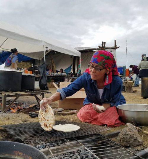 Osh Johnson, de la Nation Diné, cuit le pain pour le déjeuner au Camp Sacred Stones, l'un des trois camps établis le long de la Rivière Cannon Ball dans le Dakota du Nord où logent les opposants à l'oléoduc de Dakota Access. Photo : Pas de Dakota Access dans le Territoire du Traité - Camp Sacred Stones