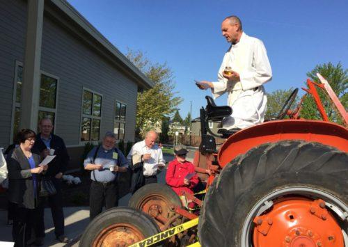 El Rdo. Jim Eichner, rector de la iglesia episcopal de la Santa Cruz en Redmond, Washington, bendice un vehículo de la Granja del Banco de Alimentos. Foto de la iglesia episcopal de la Santa Cruz.
