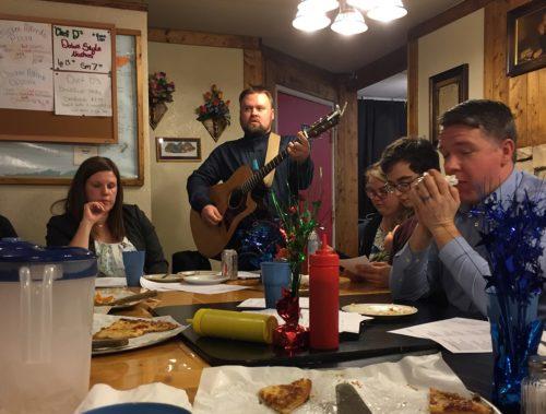 Greg Mazunik toca la guitarra en una reunión de Partiendo el Pan celebrada en una pizzería. Foto de Breaking Bread.