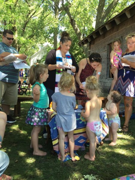 La Rda Lydia Bucklin se prepara para bautizar a su hijo Corson (a la derecha de la mesa) y a su hija Isla (con el bañador rosado) en la Feria del Estado de Iowa. Foto de Breaking Bread.