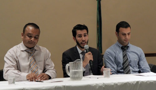 Maher Shakir, center, a former Iraqi refugee, shares his experience during a Sept. 14 panel discussion on refugee resettlement. Jay Subedi, left, a former refugee from Bhutan, and Akram Hussein, right, also originally from Iraq, also shared their experiences. Photo: Lynette Wilson