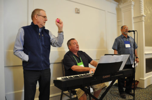 House of Bishops Music Chaplain Dent Davidson, center, plays the opening hymn during the meeting's final Eucharist. Maine Bishop Steven Lane, left, provides percussion and Dominican Republic Bishop Julio Holguín leads the signing. Photo: Mary Frances Schjonberg/Episcopal News Service