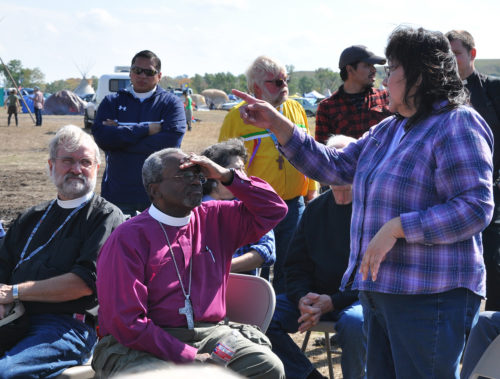 Carmen Goodhouse, a full-blood Hunkpapa Lakota and a third-generation Episcopalian, speaks with Presiding Bishop Michael Curry during a listening time Sept. 24 at Oceti Skowin Camp. South Dakota Bishop John Tarrant is beside Curry. The Rev. John Floberg, behind Curry, arranged the session. Floberg is supervising priest of the Episcopal churches on the North Dakota side of Standing Rock Reservation. Former Executive Council member the Rev. Brandon Mauai, left of Floberg, also welcomed Curry to the camp. Photo: Mary Frances Schjonberg/Episcopal News Service