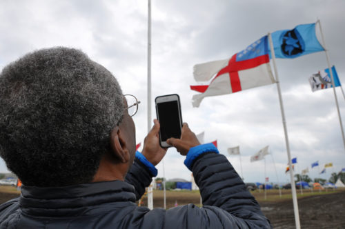 At Oceti Skowin Camp on Sept. 24, Presiding Bishop Michael Curry snaps a photo of the Episcopal Church flag marking the gathering place for Episcopalians and others at the camp north of the Cannonball River where opponents of the Dakota Access Pipeline have been living. Photo: Mary Frances Schjonberg/Episcopal News Service