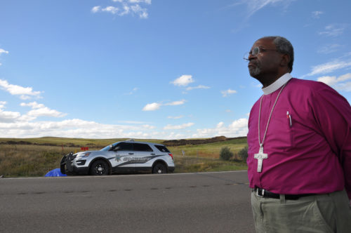Presiding Bishop Michael Curry stands along North Dakota Highway 1806 on Sept. 24 to witness as law enforcement officers arrive at a small anti-Dakota Access Pipeline encampment to arrest people accused of removing no-trespass signs from neighboring ranch land recently purchased by the pipeline construction company. Photo: Mary Frances Schjonberg/Episcopal News Service