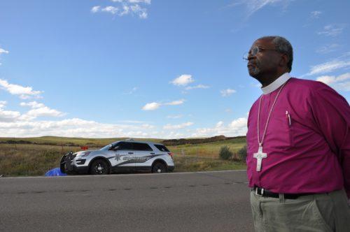 El obispo primado Michael Curry junto a la Autopista 1806 de Dakota del Norte el 24 de septiembre para presenciar como agentes de la fuerza pública llegaban a un pequeño campamento de los que protestan contra el llamado Oleoducto para el Acceso a las Dakotas para arrestar a varias personas acusadas de quitar los letreros de 'prohibido el paso' en el terreno de un rancho vecino comprado recientemente por por la compañía que construye el oleoducto. Foto de Mary Frances Schjonberg/ENS.