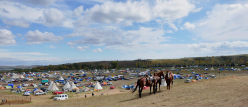 The Oceti Sakowin Camp, of Camp of Sacred Stones, spreads out along the north side of the Cannonball River on the Standing Rock Sioux Reservation. This is the view from Facebook Hill, where media have gathered, where people can charge their electronic devices at a mobile solar panel truck and where one can sometimes get a cell phone signal. Photo: Mary Frances Schjonberg/Episcopal News Service