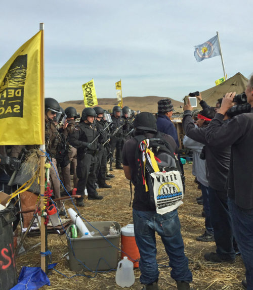Law-enforcement authorities form a line Oct. 27 as they prepare to evict a new camp of Dakota Access Pipeline opponents from the sides of Highway 1806. Photo: Caroline Grueskin via Twitter