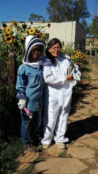 Paula Elmore, right, and her daughter, Savanna, work the bees at at Good Shepherd Mission in Fort Defiance, Arizona.