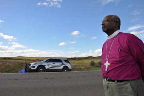 L'évêque Primat Michael Curry sur le bord de la route North Dakota Highway 1806, le 24 septembre, observe l'arrivée des forces de l'ordre sur le petit campement anti-oléoduc Dakota Access pour arrêter des personnes accusées d'avoir retiré les panneaux « propriété privée » d'un ranch voisin, récemment acheté par la compagnie qui construit l'oléoduc. Photo: Mary Frances Schjonberg/Episcopal News Service