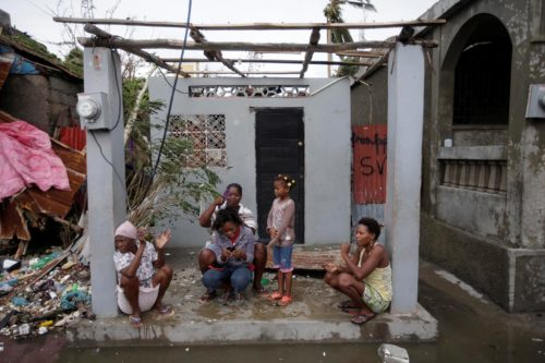 Women sit at the entrance of a house damaged by Hurricane Matthew in Les Cayes, Haiti. Photo: REUTERS/Andres Martinez Casares
