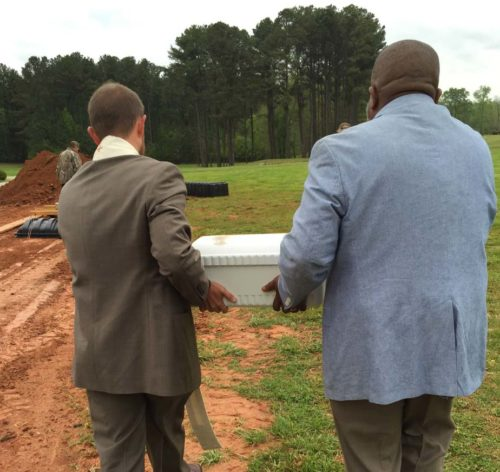 The Rev. Joshua Case (left) and the Rev. Cliff Dawkins carry the body of a child to a burial site after a service in April at Lakeside Memorial Gardens Cemetery. Photo: Joshua Case