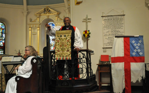Presiding Bishop Michael Curry preaches Oct. 21 at Christ Church in New Brunswick, New Jersey, as House of Deputies President Gay Clark Jennings listens. The church is a short walk from where the Episcopal Church's Executive Council was meeting. Council members joined the Christ Church congregation for Eucharist. To Curry's right is the Episcopal Church flag that flew over the Dakota Access Pipeline camp in North Dakota. Photo: Mary Frances Schjonberg/Episcopal News Service