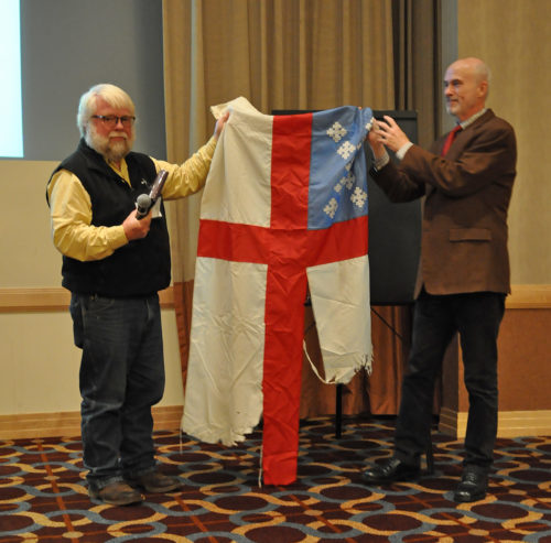 """This flag has flown so proudly,"" in part because it was the only Christian church flag at the Dakota Access Pipeline camp in North Dakota, the Rev. John Floberg told Episcopal Church Canonical Archivist Mark Duffy, right, as he presented the flag to his care. ""And we hate to give her up,"" Floberg added, his voice faltering. Photo: Mary Frances Schjonberg/Episcopal News Service"