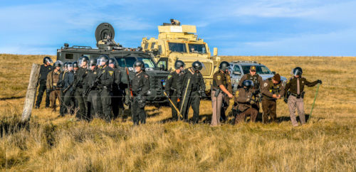 Law-enforcement officers, some dressed in riot gear and one with a rifle, wait Oct. 22 as others cut through a ranch fence to get nearer to protestors. Photo: Rob Wilson Photography via Facebook