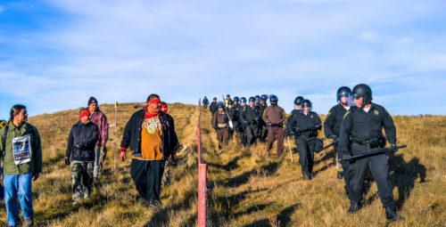 Individuos obviamente desarmados que se oponen al oleoducto marchan del otro lado de una cerca donde se alinean un destacamento de policías armados cerca del sitio de la construcción. Foto de Rob Wilson vía Facebook