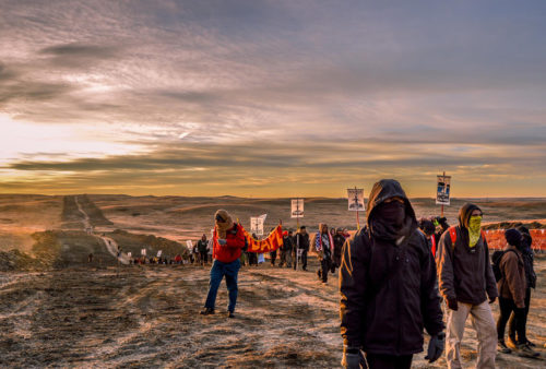 Dakota Access Pipeline project opponents, in an effort to reach protestors locked to a vehicle at a construction site, march down a path carved by the construction company through sacred ground. Photo: Rob Wilson Photography via Facebook