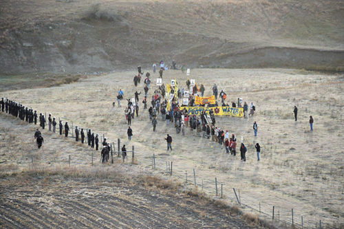Dakota Access Pipeline project opponents and law enforcement officers face off with a fence between them near a pipeline construction site. Photo: Morton County Sheriff Department via Facebook