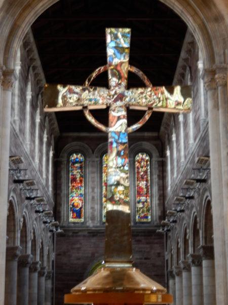 Les vitraux de la Cathédrale anglicane Sainte Anne de Belfast se reflètent sur la croix du maître autel.
