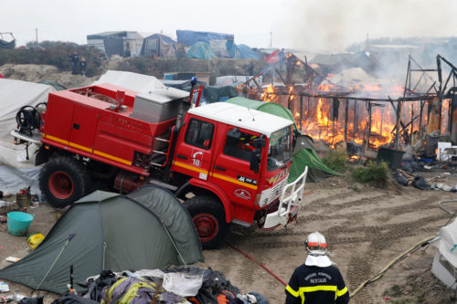 """French firemen work near burning makeshift shelters in the """"Jungle"""" on the third day of the evacuation and transfer of migrants to reception centers in France, as part of the dismantlement of the camp in Calais, France, Oct. 26. Photo: REUTERS/Pascal Rossignol"""