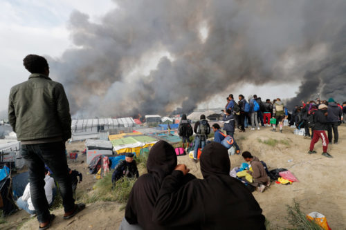 "Migrants look at burning makeshift shelters and tents in the ""Jungle"" on the third day of their evacuation and transfer to reception centers in France, as part of the dismantlement of the camp in Calais, France, Oct. 26. Photo: REUTERS/Philippe Wojazer"