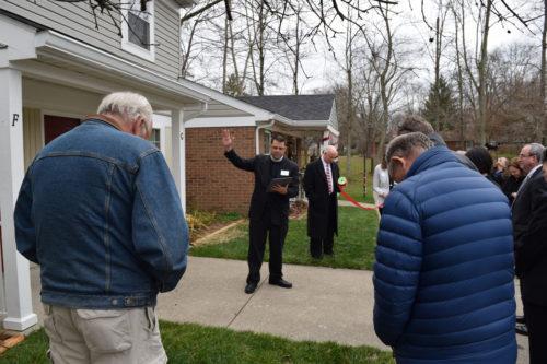 The Rev. Darren Eli blesses the renovated apartments. Photo: St. Thomas Church