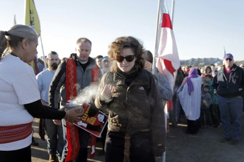 Eliza Marth, an Episcopal Service Corps fellow in Massachusetts, is smudged as she leaves the Oceti Sakowin Camp to march north along Highway 1806 to the front line where opponents of the Dakota Access Pipeline's route have been in a standoff with law enforcement officials since last week. Photo: Lynette Wilson/Episcopal News Service
