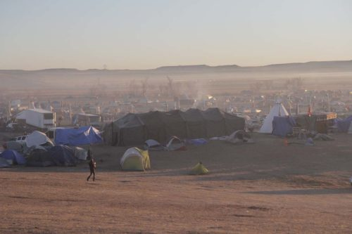 The sun rises over Oceti Sakowin Camp just north of the Cannonball River where 2,000 opponents of the Dakota Access Pipeline have been living. Opponents began arriving in small numbers in April. Larger numbers came in July and August and more continue to arrive every day. Lynette Wilson/Episcopal News Service