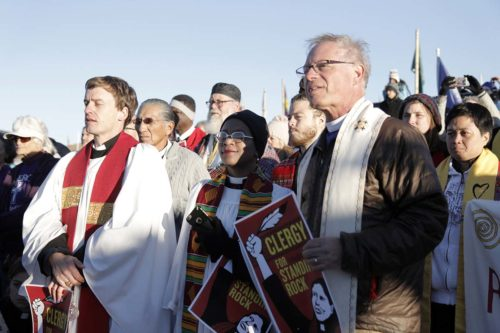 The Rev. Stephanie Spellers, canon to the presiding bishop for evangelism and reconciliation, and California Bishop Marc Andrus join a circle of more than 500 interfaith allies standing in prayerful, peaceful solidarity with the Standing Rock Sioux Nation in their opposition to the route of the Dakota Access Pipeline. Photo: Lynette Wilson/Episcopal News Service