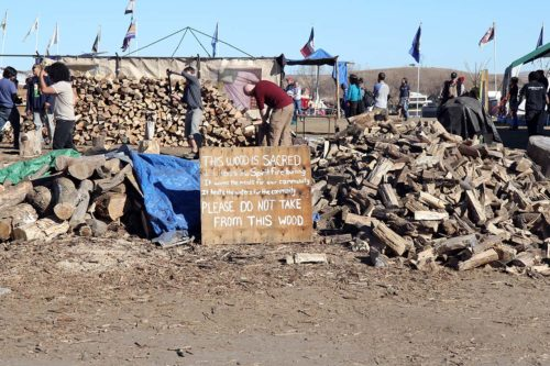 Firewood from this pile keeps the sacred fire burning around the clock in the center of the Oceti Sakowin Camp. Photo: Lynette Wilson/Episcopal News Service