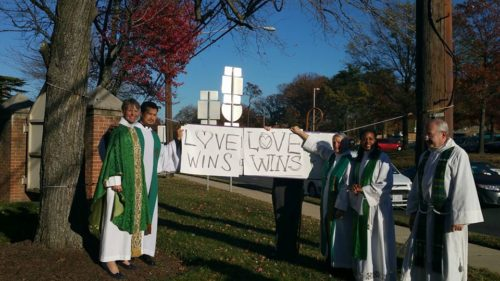 "To the left, Washington Bishop Mariann Budde and the Rev. Francisco Valle, assistant priest and leader of the Spanish-language Mass at Church of Our Saviour in Silver Spring, Maryland, hold a sign that reads ""Love Wins"" following an incident of racist vandalism at the church over the weekend. The Rev. Robert Harvey, the churches rector, on the right in the foreground, and others join them. Photo: Facebook"