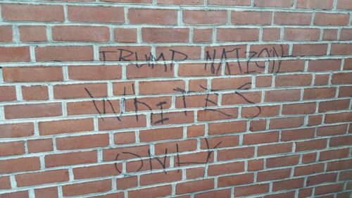 "Vandals wrote ""Trump Nation Whites Only"" on the red-brick wall in Church of Our Saviour's memorial garden. Photo: Facebook"