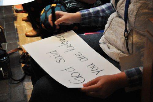 """En un ejercicio el día de la clausura de La evangelización es importante, los participantes aprenden acerca de """"testimonios en cartón"""", al escribir por una cara del pliego sobre algo con lo cual tienen problema y, por el otro lado, lo que Dios ha hecho por ellos respecto a ese problema. Foto de Mary Frances Schjonberg/ENS."""