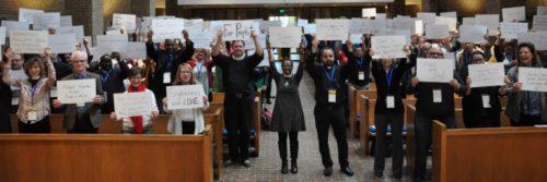 """Participantes de la conferencia La Evangelización es importante presentan sus """"testimonios en cartón"""" primero por el lado de su problema (arriba) y, aquí, por el lado de Dios obrando en el problema. Foto de Mary Frances Schjonberg/ENS."""