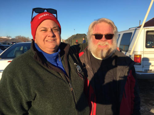 "The Rev. Lauren Stanley, superintendent presbyter of the Rosebud Episcopal Mission West in South Dakota, wears a read beanie with ""chaplain"" written across the front, while standing alongside the Rev. John Floberg, supervising priest of the Episcopal churches on the North Dakota side of Standing Rock. Photo: Paul J. Lebens-Englund/Facebook"